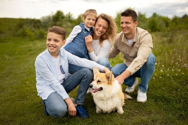 Famiglia felice a tutto campo con un cane carino