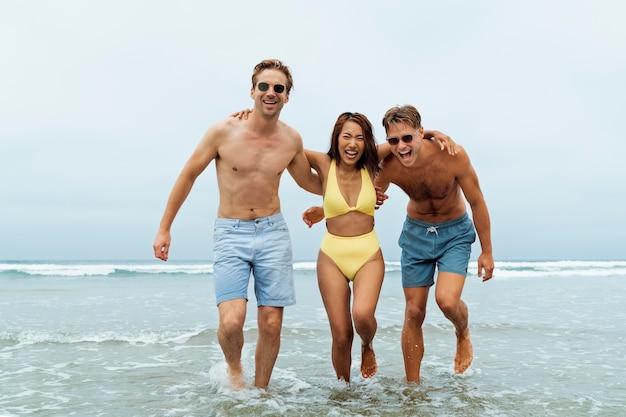 海辺でのフルショットの幸せな友達