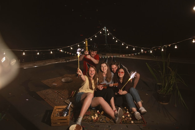 Amici felici a tutto campo con fuochi d'artificio