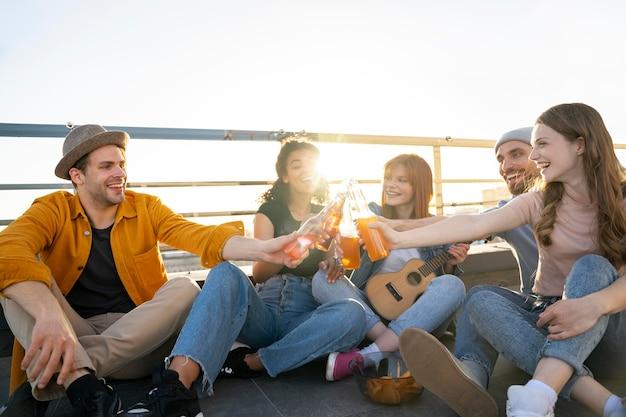 Полный кадр счастливых друзей с гитарой