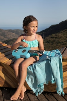 Full shot happy girl with guitar