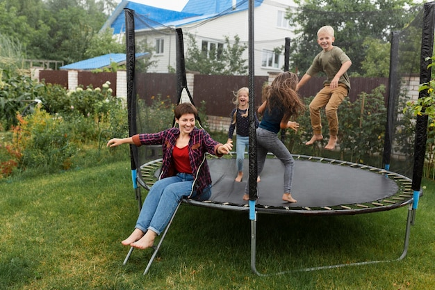 Bambini felici a tutto campo che saltano sul trampolino