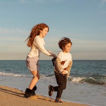 Полный снимок счастливых детей, бегущих на берегу