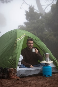 Full shot happy man in tent