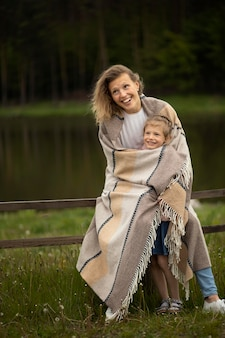 Full shot happy mother and kid with blanket