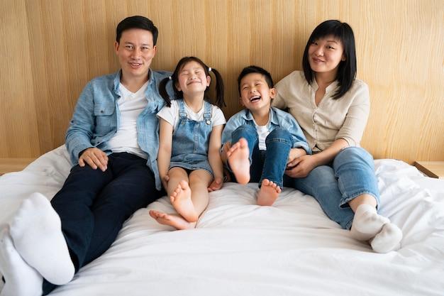 Полный снимок счастливых родителей и детей в постели