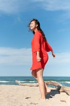 Donna felice a tutto campo in spiaggia?