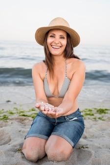 모래에 앉아 전체 샷된 행복 한 여자