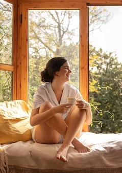 Donna felice del colpo pieno con la tazza