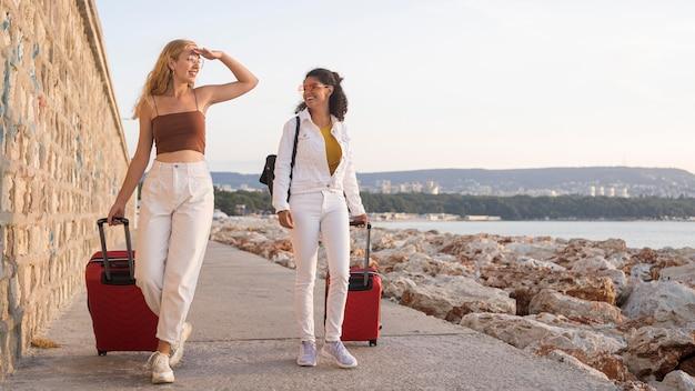 Donne felici del colpo pieno che trasportano i bagagli