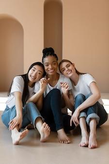 Donne felici del colpo pieno che si siedono sul pavimento