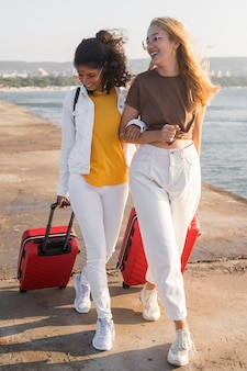 Full shot happy women traveling with luggage