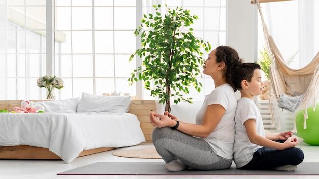Full shot kid and adult meditating together