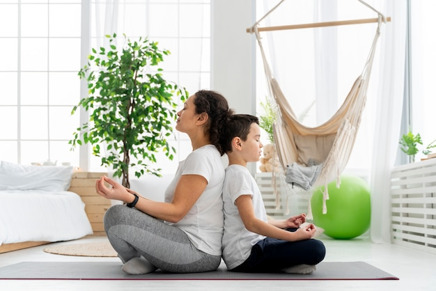 Full shot kid and adult meditating