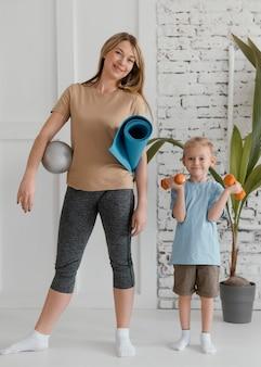 Полный выстрел ребенок и женщина со спортивным оборудованием