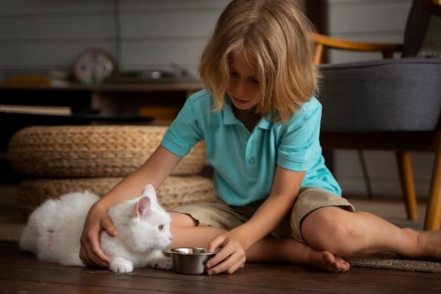Gatto a tutto campo che dà da mangiare a un bambino