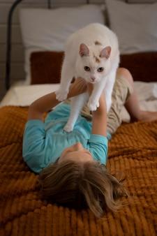 Полный снимок ребенка, держащего очаровательную кошку в постели