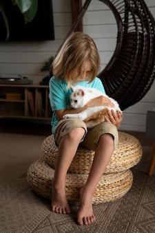 Полный выстрел ребенок держит кошку
