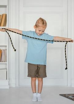 Ragazzo pieno del colpo che tiene la corda di salto