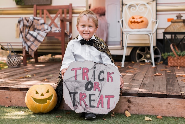 Full shot kid holding trick or treat sign
