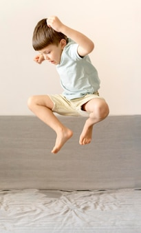 Full shot kid jumping on couch