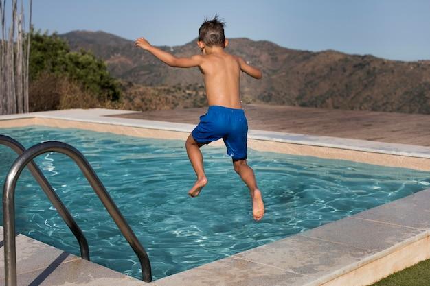 Full shot kid jumping in poll