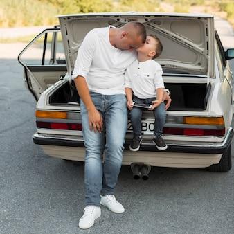 Full shot kid kissing father on head