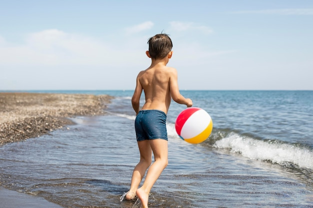 Full shot kid playing with ball at beach