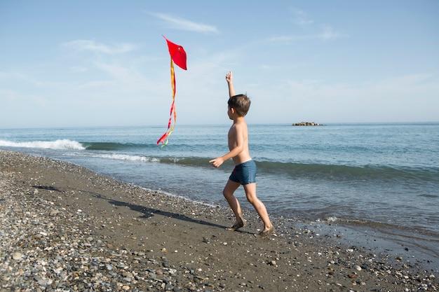 Full shot kid playing with kite