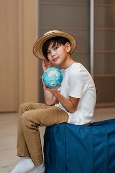 Full shot kid posing on luggage