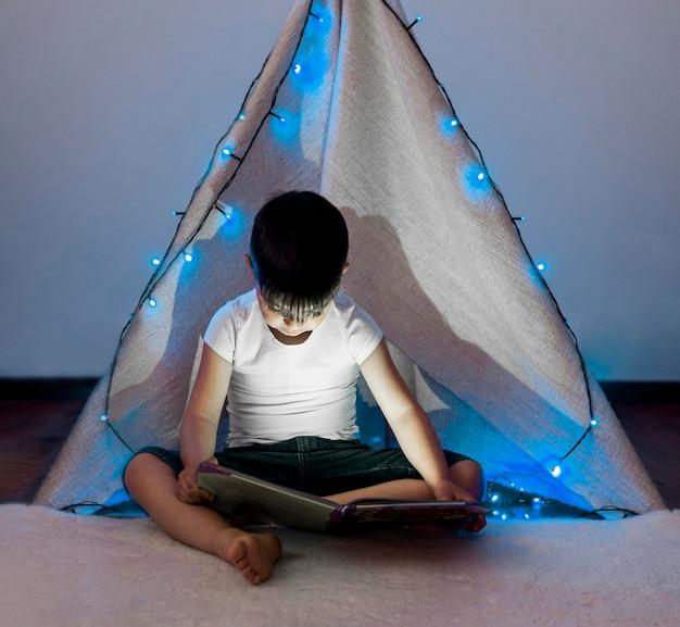 Full shot kid reading in tent