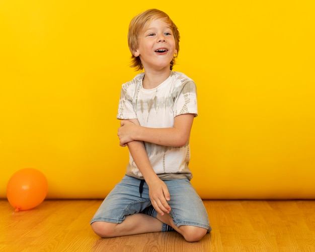 Full shot kid sitting on floor