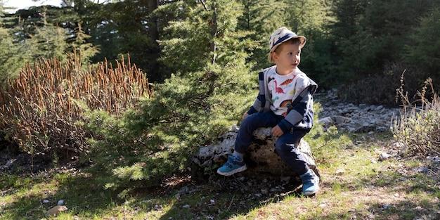 自然の中で座っているフルショットの子供