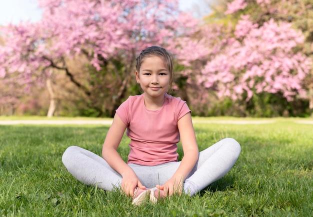 Полный ребенок сидит на траве