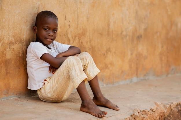 屋外に座っているフルショットの子供