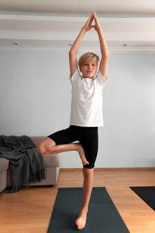 Full shot kid standing on one leg