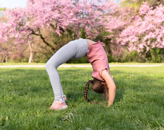 Полный ребенок, тренирующийся на траве