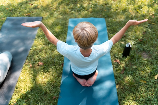 Full shot kid on yoga mat