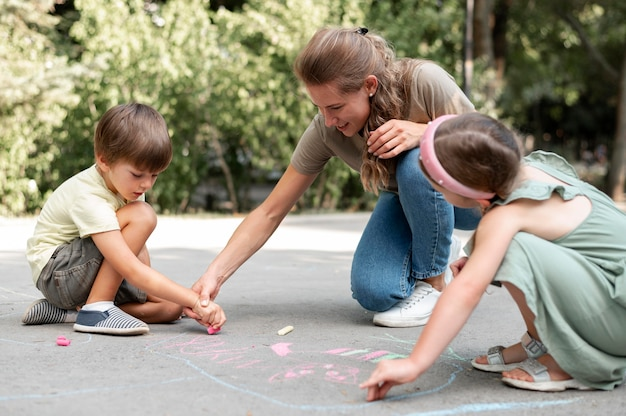 Полный кадр дети и учитель рисуют на земле