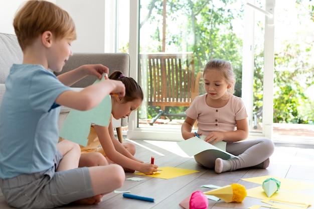 Bambini a tutto campo che sono creativi con la carta