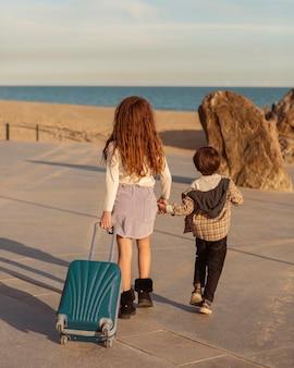 手荷物を運ぶフルショットの子供たち