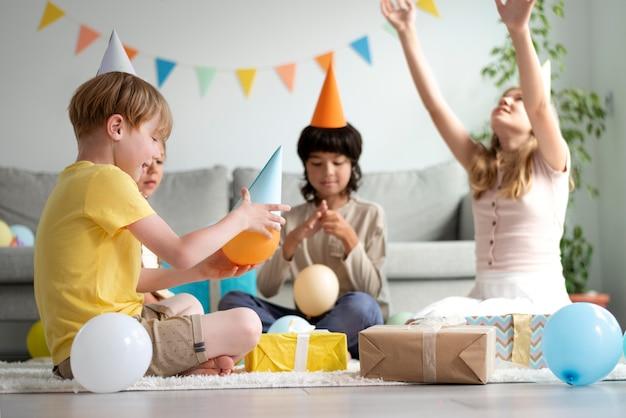 Bambini a tutto campo che festeggiano il compleanno con i palloncini