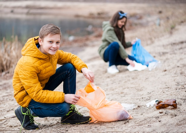 Full shot of kids cleaning the ground