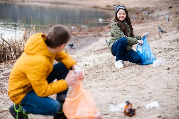 Colpo pieno di bambini che puliscono il terreno