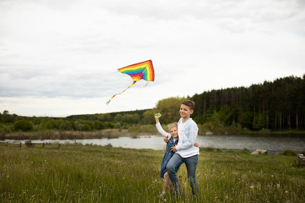Full shot kids flying a kite together