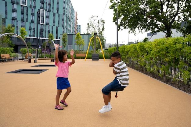 公園で楽しんでいるフルショットの子供たち