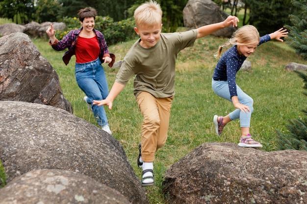 岩の上をジャンプするフルショットの子供たち