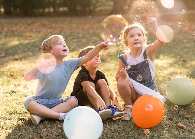 屋外で遊ぶフルショットの子供たち