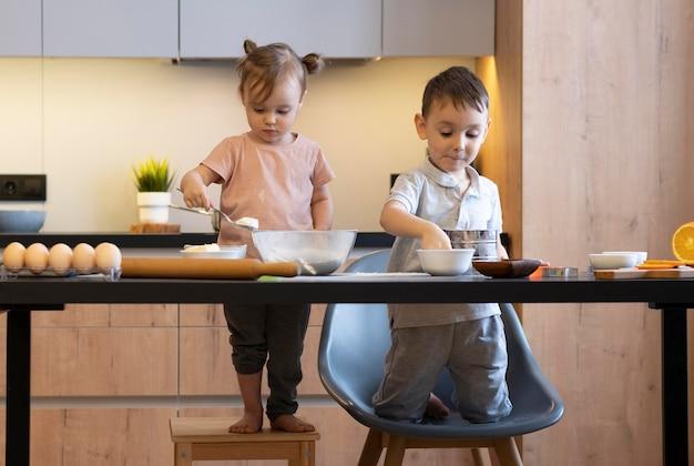 Bambini del colpo pieno che preparano il pasto insieme