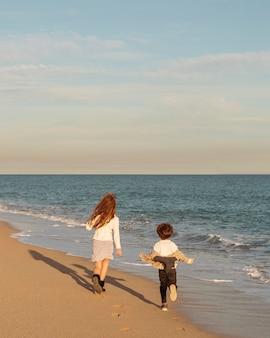 Полный снимок детей, бегущих на берегу